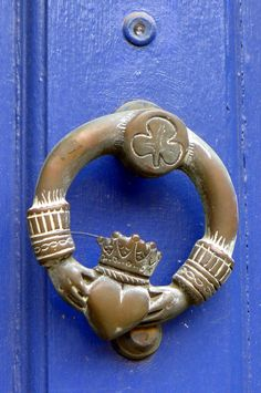 Door knocker in the shape of an Irish Claddagh ring . A Claddagh ring shows two hands holding a heart which wears a crown.
