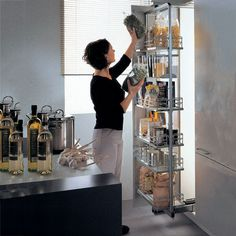 Kessebohmer swing pull out pantry frame pivots left and right when the storage unit is fully extended, provides access to both sides of tray and wire basket inserts, plus allows unit to remain open and flush against cabinets during extended periods of use.
