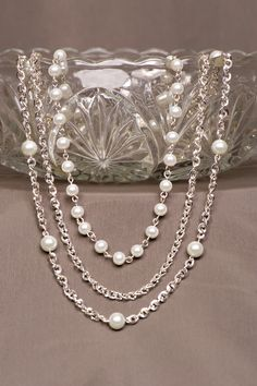 Item 14250:  Triple strand silver-plated chain necklace with white glass pearls.  Slide lock clasp $35.00