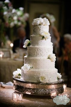 Set atop an ornate silver stand, this wedding cake features five exquisite layers, each carefully detailed with white frosted swirls and dots. White peonies scattered across the tops and sides of the cakes complete the elegant confection, which was served at the Carnegie Music Hall Foyer in Pittsburgh. The John Parker Band had the honor of playing for the bride and groom at their wedding reception. Their music kept the guests dancing throughout the whole party…