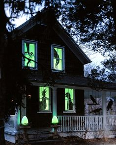 This is so easy. Cut out any scary shapes on black cardboard, tape to window panes, cover with green tissue paper and light from behind. Its a great effect.