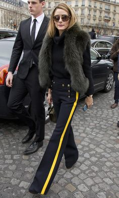 Olivia Palermo wears a ribbed turtleneck, wide-leg trousers, a shaggy est, Analeena micro-lady day bag, and sunglasses