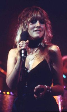 beautiful Stevie onstage, wearing the gold teddy bear necklace she got from a fan while performing with the other members of  Fleetwood Mac at the Summit in Houston, Texas - May 16th, 1977, and biting her lower lip ~ such a cute habit of hers ~   ☆♥❤♥☆ ~