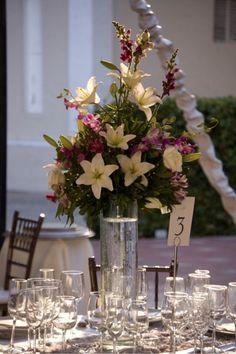 Altos y ElegantesAltos y Elegantes lucen estos centros de mesa elaborados con lilis blancas y orquídeas y alstroemerias en tonos morados, puestos en una base de cristal llena de agua que a la hora de iluminar el evento lucirán muy llamativos.