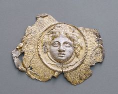 Appliqué with Medusa, Greek, possibly from South Italy, 300 - 275B.C.Silver and gold    This gilded silver relief attachment represents the aegis, a breastplate made of goatskin fringed with snakes that provided the goddess Athena with magical protection. A gorgoneion, the severed head of the monstrous gorgon Medusa, given to Athena by the hero Perseus forms the center of the aegis.