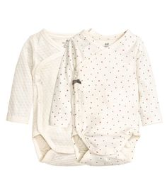 Natural white/dotted. CONSCIOUS. Long-sleeved, wrapover bodysuits in soft organic cotton jersey with snap fasteners at one side and at gusset.