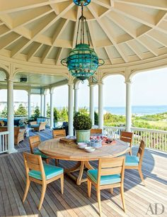 The dining area of a Hamptons porch is centered by an ornate light fixture | archdigest.com