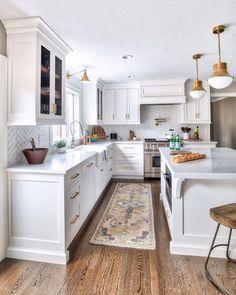 White herringbone backsplash, white cabinets, white countertops