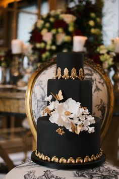 From Elizabeth's Cake Emporium a black wedding cake with gold baroque embellishments, white sugar peony and gold butterflies