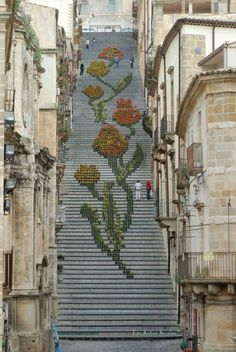 Located in the Sicilian town of Caltagirone, La Scala di Santa Maria del Monte is an old 142-step staircase, each of which are decorated with a different ceramic pattern. It's a wonder to behold, but during the Spring and Summer seasons it becomes even more breathtaking as locals adorn it with potted flowers and lanterns, creating intricate designs.
