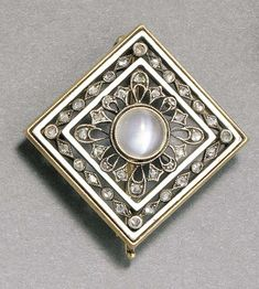 A JEWELLED GOLD-MOUNTED ENAMEL BROOCH  by Fabergé and with the workmaster's mark of August Holmström, St. Petersburg, 1896-1908 The cabochon moonstone set into two white opaque enamel square frames enclosing a stylized design set with rose-cut diamonds, marked on pin and clasp