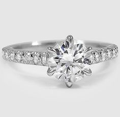 Glamorous French pavé set diamonds sparkle along this ring and beautifully accent the center diamond, which is secured in a timeless six prong setting designed to showcase its brilliance. ==