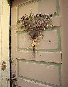 Old rake head repurposed to door decor. I even love the flower colors used... May have to try to find an old rake for this one.