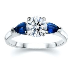Round diamond with pear shaped blue sapphire side stones complimenting this three stone ring