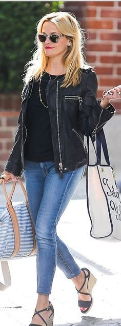 Reese Witherspoon's black top, blue leather jacket, wedge sandals, clear sunglasses, white handbag, and skinny jeans