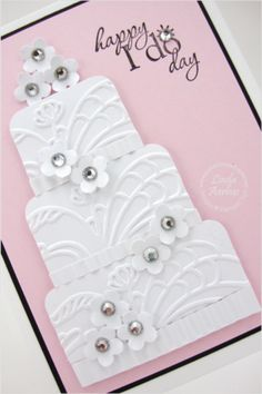 Wedding cake card using embossing, punches, aand rhinestone accents, against a pink background