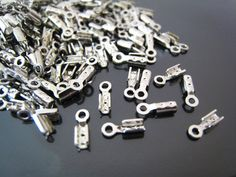 Finding - 20 pcs Silver Small Crimps Tone Fold Over Cord Ends Caps With Loop ( 8mm x 3mm ). $1.99, via Etsy.