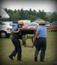 Two Amish men carrying a treadle machine that they purchased for one of their wives.