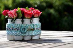 Decore a sua mesa de forma primorosa, porém bem barata, com um centro de mesa com potes reciclados.