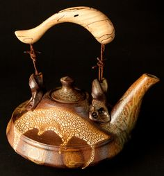 """Larry Spears     Spiked Tea II    A truly one-of-a-kind piece with precise attention to detail; this unique teapot is designed for function or a truly great piece of hand-made art; hand-thrown stoneware, with wood-ash and crawl exterior glazes; durable celadon liner glaze. The handle is hand-carved maple and attached to the piece with antique barbed-wire. 9 ½"""" diameter (including spout) x 9 ½"""" height (including handle) x 3"""" diameter (bottom/base)."""