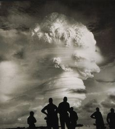 Men watch a mushroom cloud from one of 216 above-ground or underwater nuclear test explosions in the U.S. between 1945 and 1962, when they were driven underground by the Limited Test Ban Treaty.