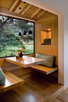 here's something very cozy about this kitchen nook design. Maybe it's the choice of wood covering the entire space, differentiating it from the exterior wall. Maybe it's the choice of lighting and soft pillows. Or maybe it's that amazing window with its exposed frame. It's probably all of those combined. The nook stays true to the minimalism throughout this contemporary home. Notice the absence of legs from the table and benches. This keeps the little nook feeling open and spacious.