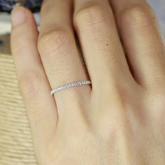 This petite diamond wedding band showcases a half circle of sparkling conflict free natural diamonds set in a solid 14k white gold half eternity