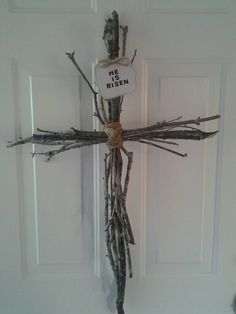 """I saw this Door Cross on pintrest and I copied it.... I made this from sticks from my yard and the """"He is Risen"""" I made from my scrapbooking stuff and used heavy duty Jute to tie it together .....less then a buck ! Perfect for my Easter deco !"""