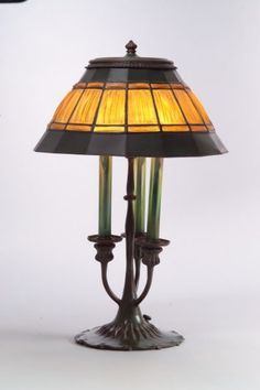 Tiffany Studios Table Lamp, Bronze and glass, New York, 20th century   Linenfold glass and bronze shade over three light candlestick lamp with pulled father cylindrical socket covers, base with circular scroll foot.