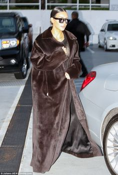Keeping cool: Kim Kardashianlooked chic as she arrived for dinner in Brentwood, California rocking a long black velvet coat