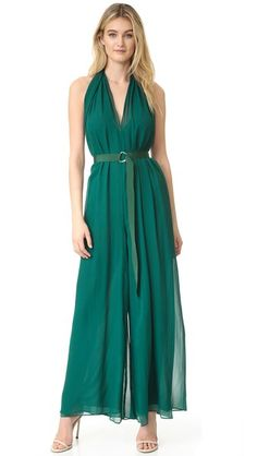 Layered, tissue-weight silk crepe composes this graceful Nicholas jumpsuit. The halter strap suspends the V neckline and twists over the open back.