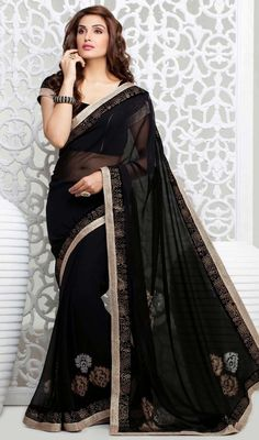 Stunning black embroidered georgette sari adds charm and grace to your beauty. The sari is garnished with woven lace and crystal stone embroidered border and motifs which enhances the look. The sari pairs with matching stitched blouse as shown in the picture. #NewTrendsetterSarees
