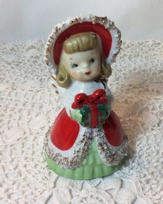 This sweet little girl angel (see her wings) is holding out a present just for you. She has an old fashioned bonnet and ruffled green dress