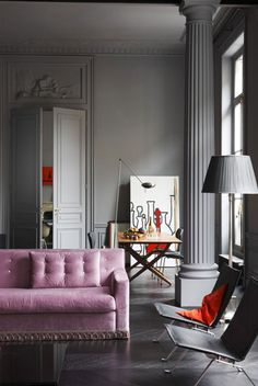 Grey walls and a pink sofa.