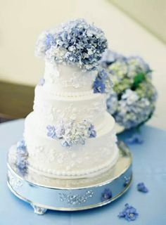 """This beautiful hydrangea topped cake would be a lavish """"something blue"""" addition to any wedding."""