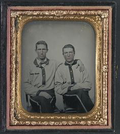 Two soldiers in Confederate battleshirts- one seems to be wearing a shirt with a necktie under the battleshirt