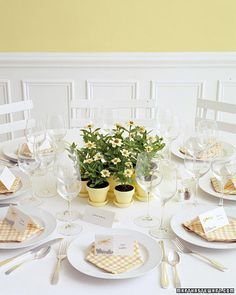 """A cluster of potted zinnias adds charm to the table at a country or casual wedding. A sign next to the display asks guests to """"Please pick one."""" The pots are painted with acrylic paint to match the flowers. The theme that inspires the favor continues at each place setting: Seeds packaged in glassine bags are attached to each of the tented place cards with yellow twine that is inserted through two small punched holes, then tied in a bow. Directions for planting are printed inside the cards."""