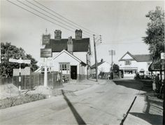 Canvey Island, Essex, England, 1930s. The village looking east. The Red Cow (now the King Canute) public house on the left, the thatched-roof water pump can just be seen on the right and the building in the middle is still standing today.