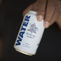 An East Porterville, CA resident holds a can of water donated by the Anheuser-Busch company as water... - Provided by Popular Mechanics