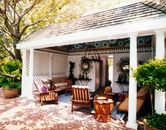 You don't have to have a pool house to pull off this look. Use similar furniture and accessories on your own covered patio to create this oasis. Antique French recliners from John Rosselli. The sofa is from Wicker Works. Drum stool from Badia Design.