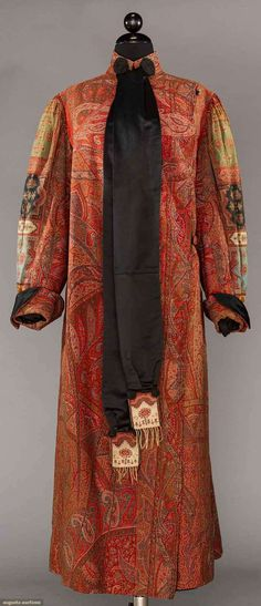 """FRENCH PAISLEY SHAWL COAT, c. 1905  Lot: 192 May 9, 2017 - CATALOG SALE Sturbridge, Massachusetts  19th C French wool paisley shawl made up as coat, bilaterally symmetrical & matched seams, sleeves gathered at shoulder & into cuff, band collar, 2 black satin ribbons w/ French """"F & Cie"""" signature to paisley, black satin lining, B 38"""", L 52"""", (inside collar worn at neck, edge channel quilted lapel worn, black silk button loops damaged, .5"""" """"L"""" tear right elbow) very good."""