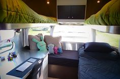 CCD bedroom refitted with a desk, 3/4 bed, 2 bunks, and a reading nook. I'm impressed with how they reconfigured the space. Timeless Travel Trailers made the bunks.