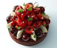 Gateaux Thoumieux -Le Cerisier est composé d'un biscuit léger cacaoté, d'un onctueux crémeux chocolat à la cerise acidulée et d'un délicieux confit de cerises. Sur le dessus, se trouvent des touches de chantilly mascarpone-vanille pochées, des cerises sucrées et gourmandes, et des pétales de chocolat, qui créent un élégant bouquet de cerises.