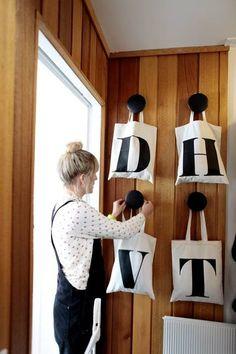 Entreens opprinnelige teakvegger bak det grafiske: knagger fra Muuto og bokstavnett fra Alphabet Bags. Hvert familiemedlem har sitt nett med daglige bruksting. (Foto: Carl Martin Nordby)