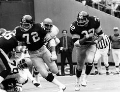 Pittsburgh Steelers running back Franco Harris (32) runs with the ball with a block from guard Gerry Mullins (72) against the Cincinnati Bengals at Riverfront Stadium. The Steelers beat the Bengals 35-14.