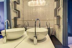 Łazienka w stylu glamour. Designerski grzejnik o niestandardowym kształcie, efektowne oświetlenie w postaci kryształowego żyrandola, płytki na wysoki połysk, wysokiej jakości ceramika i baterie łazienkowe.