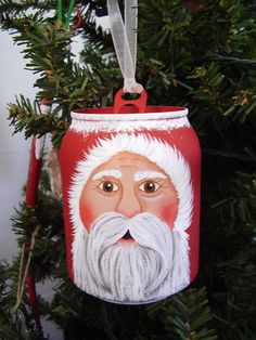 This ornament has been painted on a mini 7-Up can. It has been painted with acrylics and has a mesh-type ribbon for hanging.
