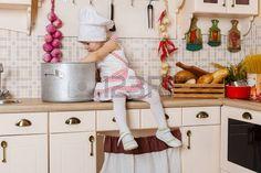 Kleines Mädchen in Schürze und Mütze des Kochs in der Küche sitzen im Haus. Mutter Helfer. 2 Jahre alt. Lizenzfreie Bilder