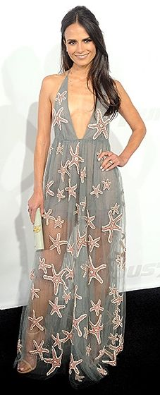 """The star kept the sheer trend alive via a gray Valentino halter dress that was covered in star appliqués. She accessorized with Stuart Weitzman """"Nudist"""" sandals and a mint-hued clutch."""