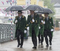 A group of smartly-dressed guests keep their tailcoats dry with giant umbrellas as they arrived at the racecourse in Berkshire. 14 June 2016.